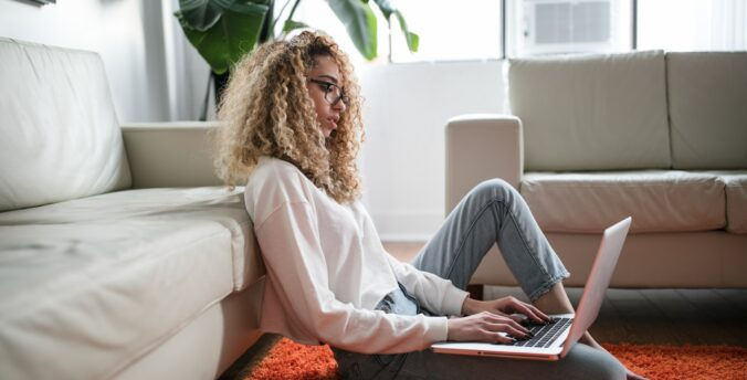 Woman on floor looking thoughtfully at laptop