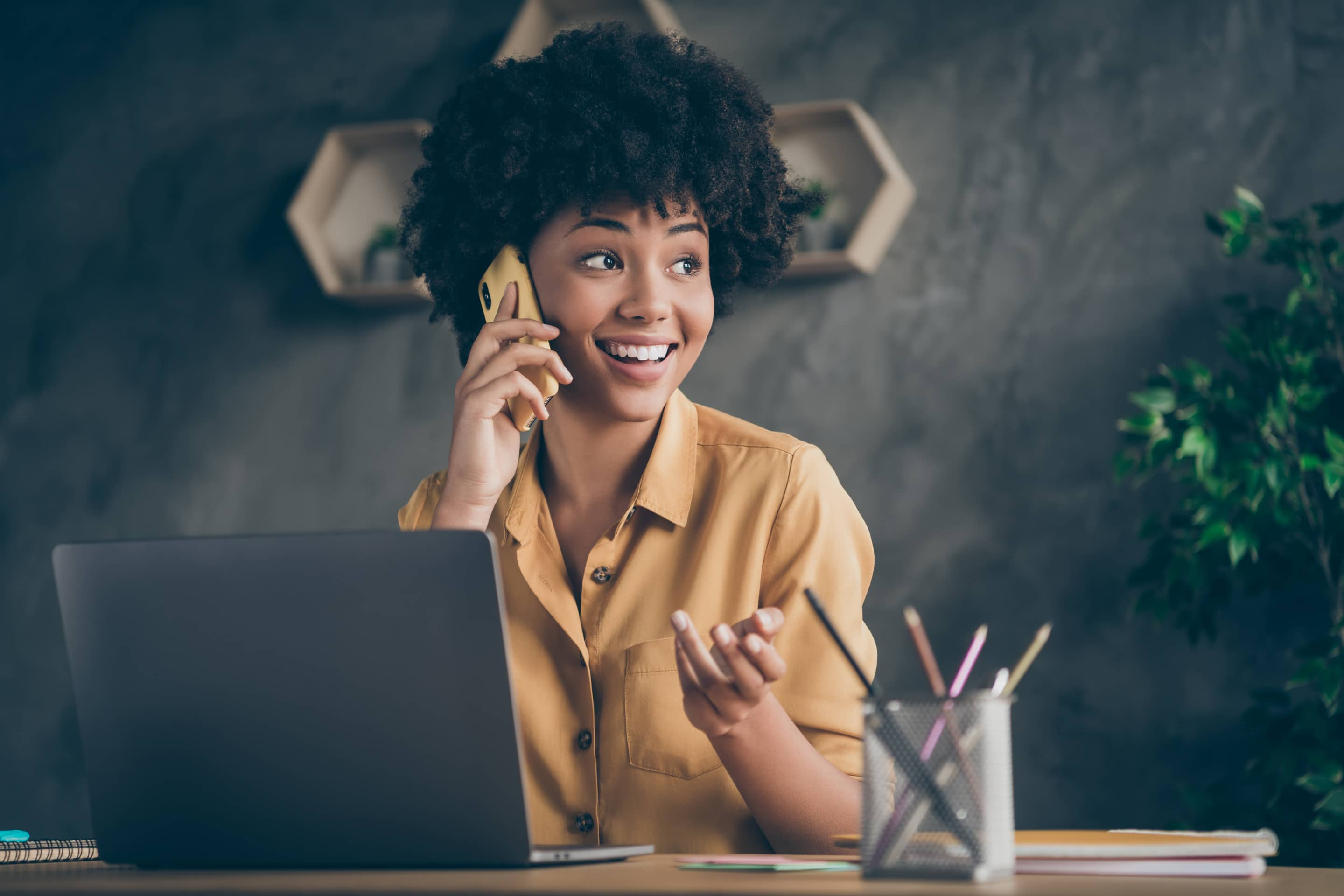 Photo Of Cheerful Positive Mixed Race Pretty Woman Working As Content Manager Arranging With Her Customers By Phone Smiling Toothily