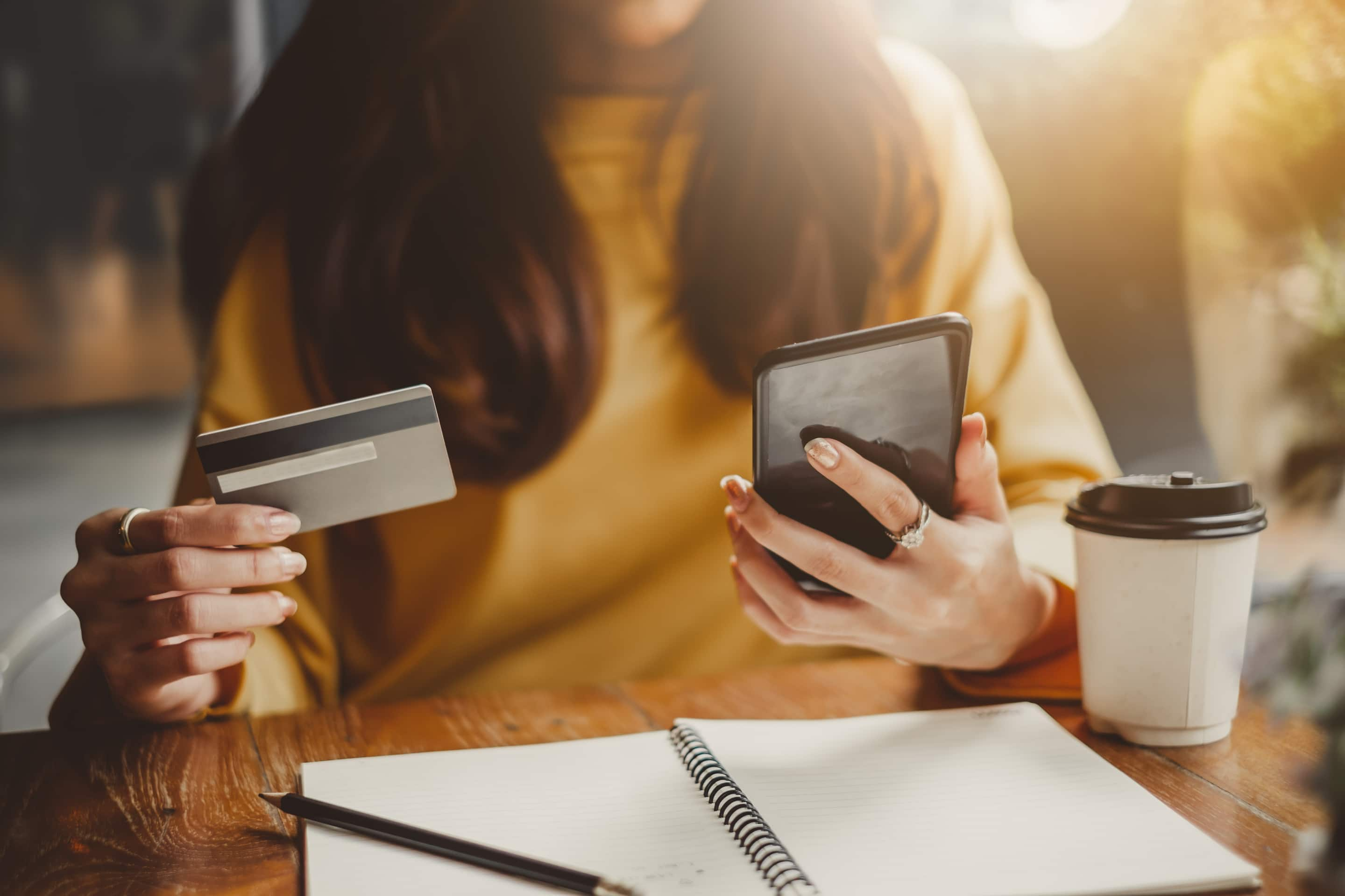 Woman Using Smart Phone And Credit Card